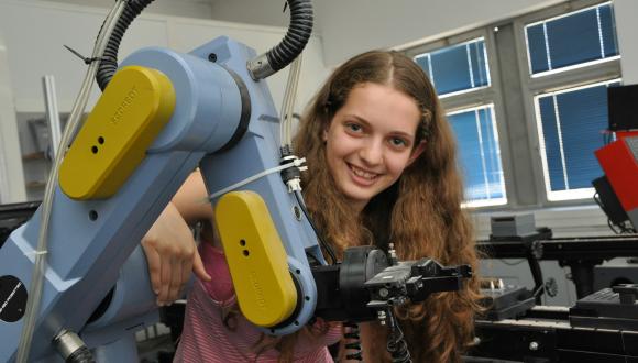 נערה מתכנית מדעני העתיד במעבדה ליד זרוע רובוטית